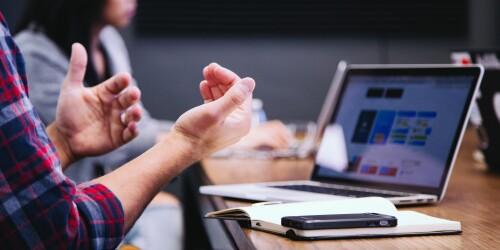 Menschen sitzen mit einem Laptop am Tisch und diskutieren.