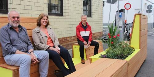 Drei Menschen sitzen auf Stadtmöbeln und lachen in die Kamera