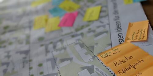 Auf einem Stadtplan kleben Zettel mit Wünschen.